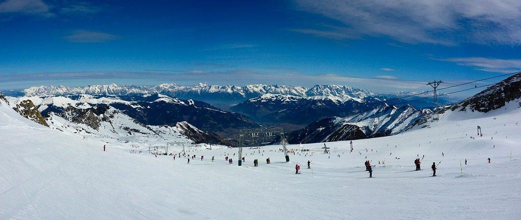 Piste met skiërs en felblauwe lucht