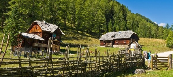 Twee wandelaars gaan door een hekje bij een huisje in de bergen