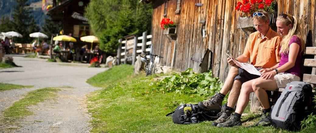 Twee wandelaars zitten op een bankje bij een hut