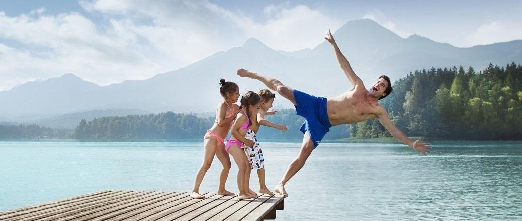 Kinderen spelen met man op steiger aan meer
