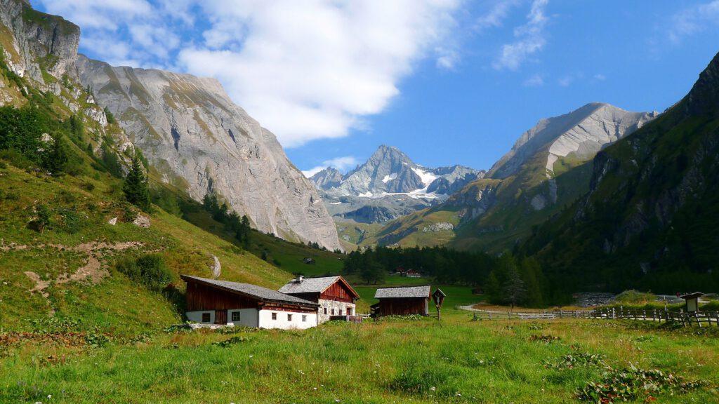 Huisje in groen veld tussen bergen