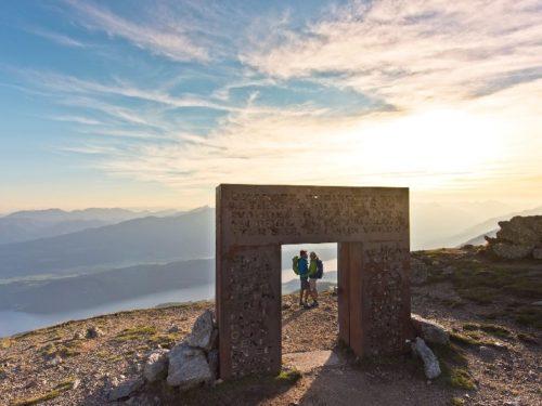 Twee wandelaars op berg bij zonsondergang