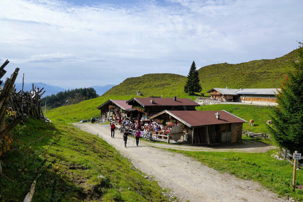 Wandelaars lopen langs een hut in de bergen