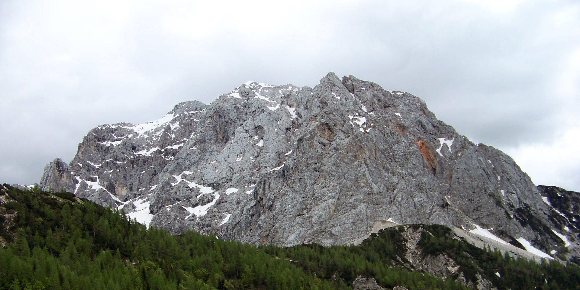 Rotsachtige bergtop met groene bomen er onder