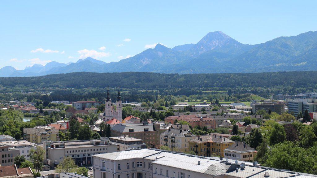 Plaats met kerkje, bergen op achtergrond