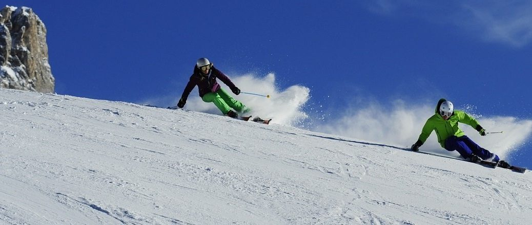 Twee skiërs op een piste