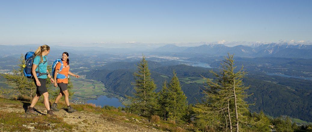 Twee wandelaars met uitzicht over meer in dal