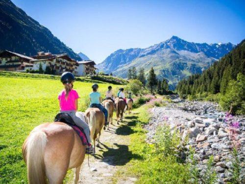 Groep kinderen op paarden rijden door dal in de bergen