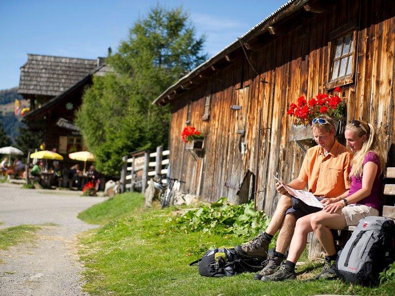 Twee wandelaars zitten bij berghut