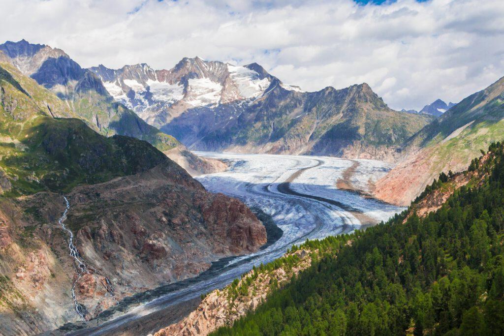 Gletsjer tussen bergen met groene bomen