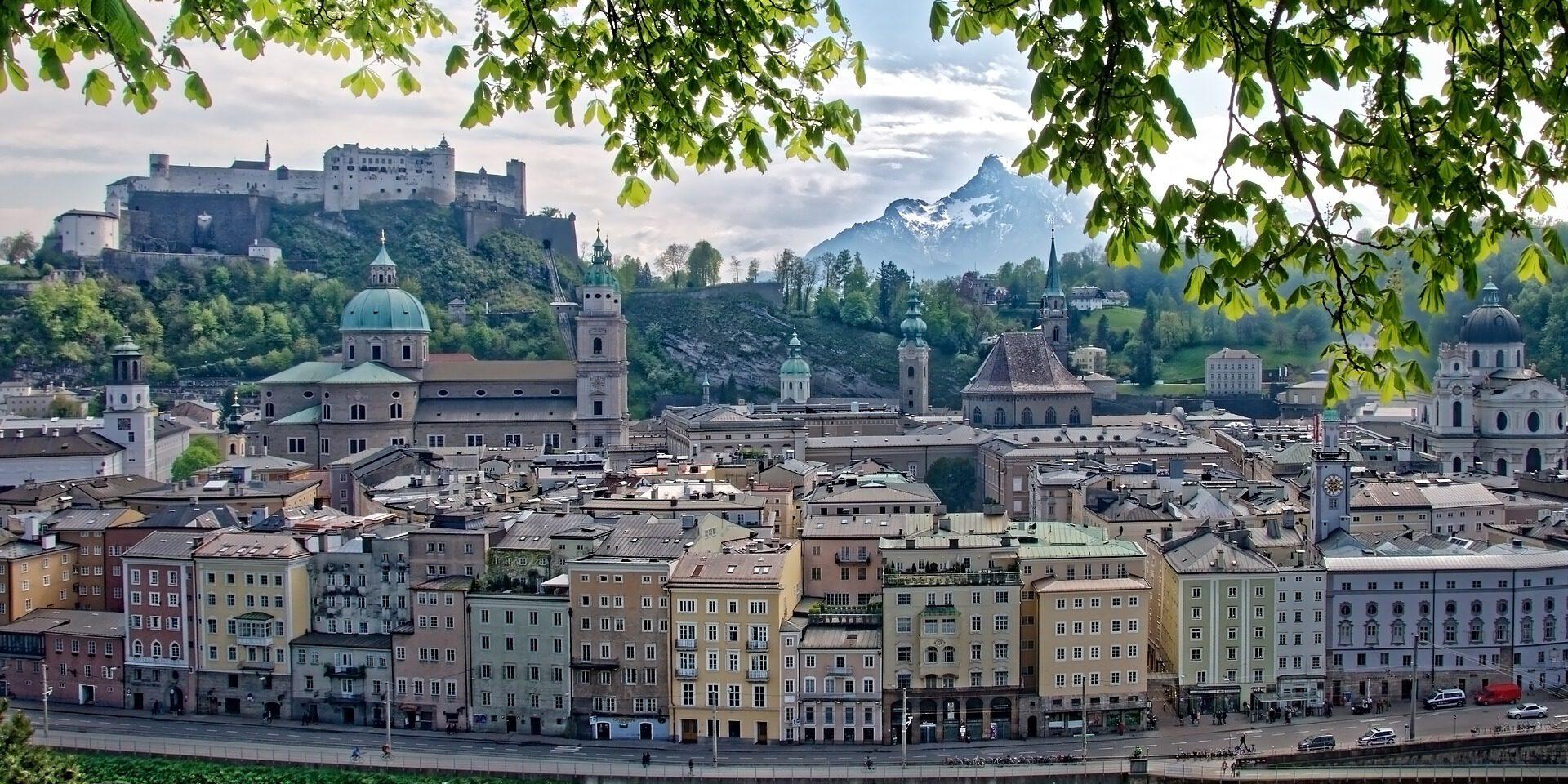 Zicht op oude stad met gekleurde gebouwen en kasteel, bladeren en takken er voor