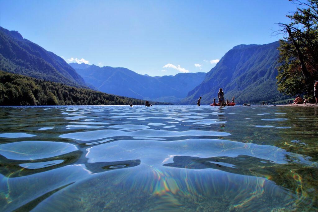 Helder meer in bergen met mensen in water