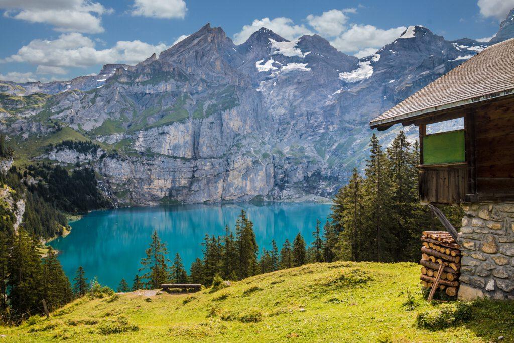 Hut bij bergmeer met bergen er achter