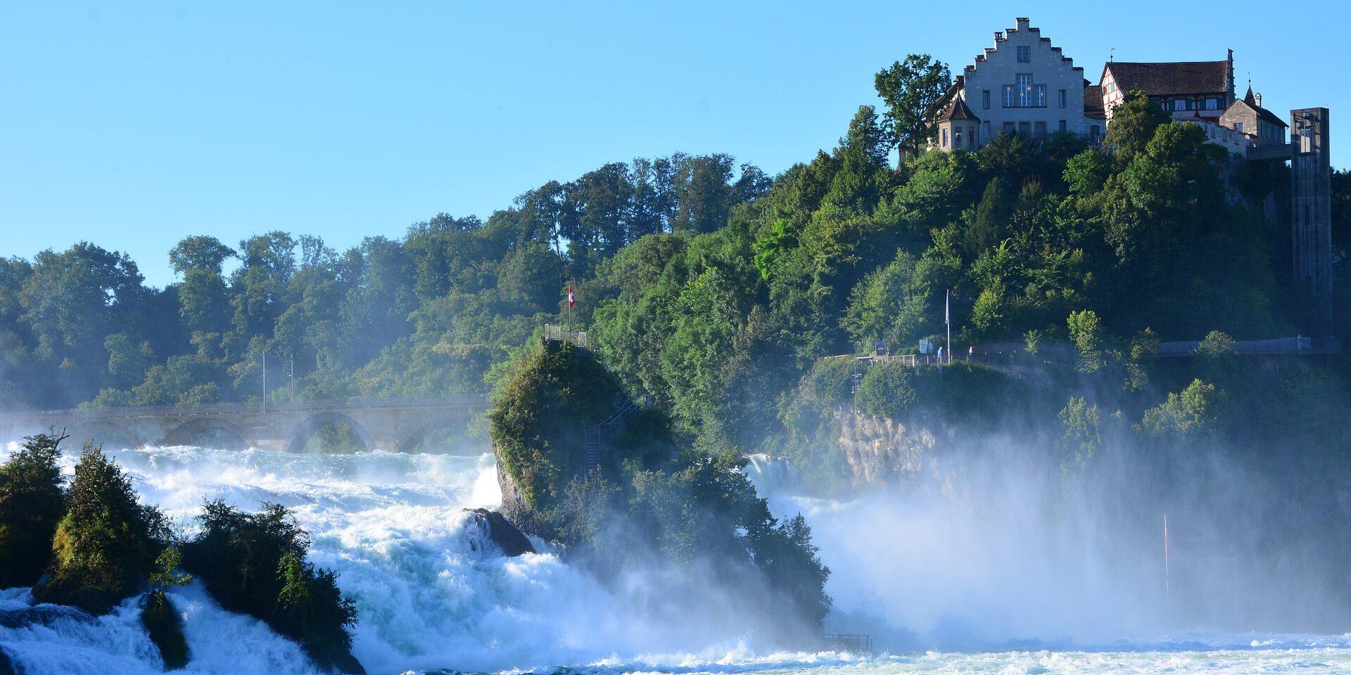 Waterval met gebouwen op rotsen
