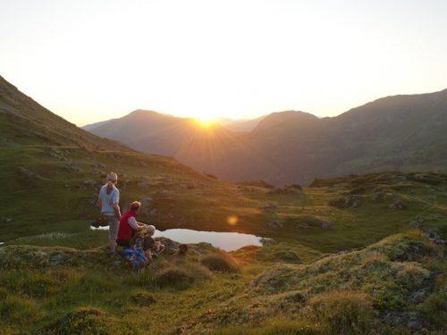 Mensen bij een klein bergmeertje bij zonsopkomst