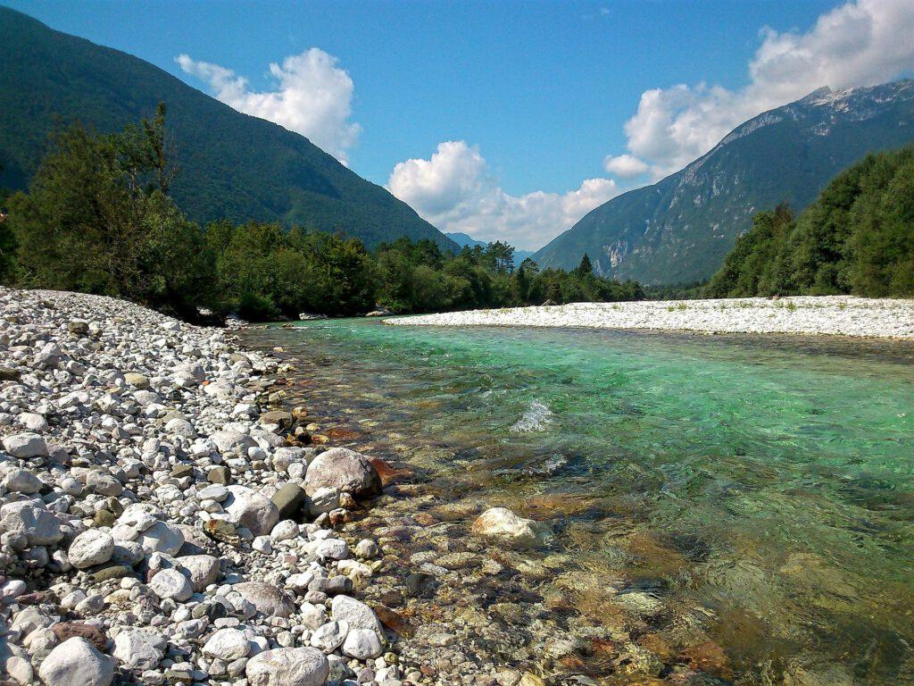 Groenblauwe rivier tussen stenen en bomen