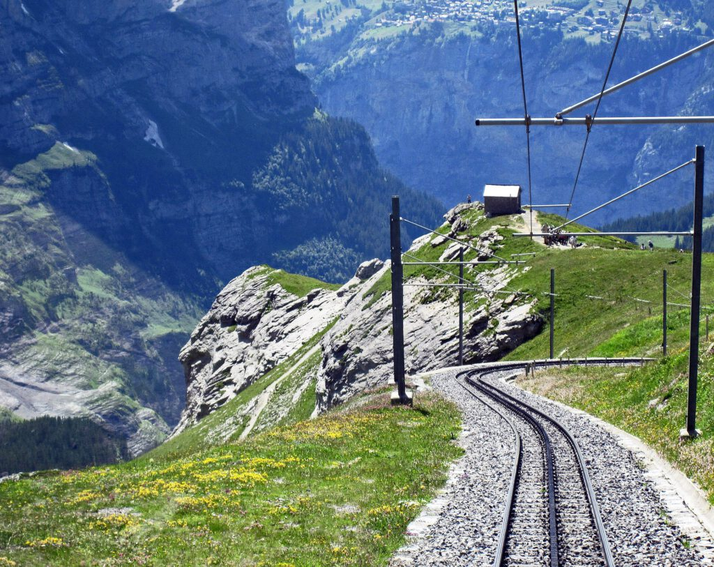Uitzicht over treinspoor in bergen met groen gras