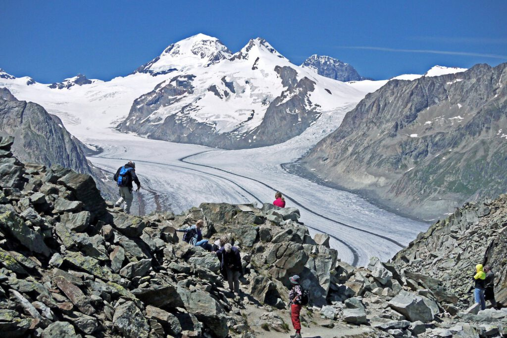 Uitzicht over gletsjer met blauwe lucht, enkele mensen op voorgrond