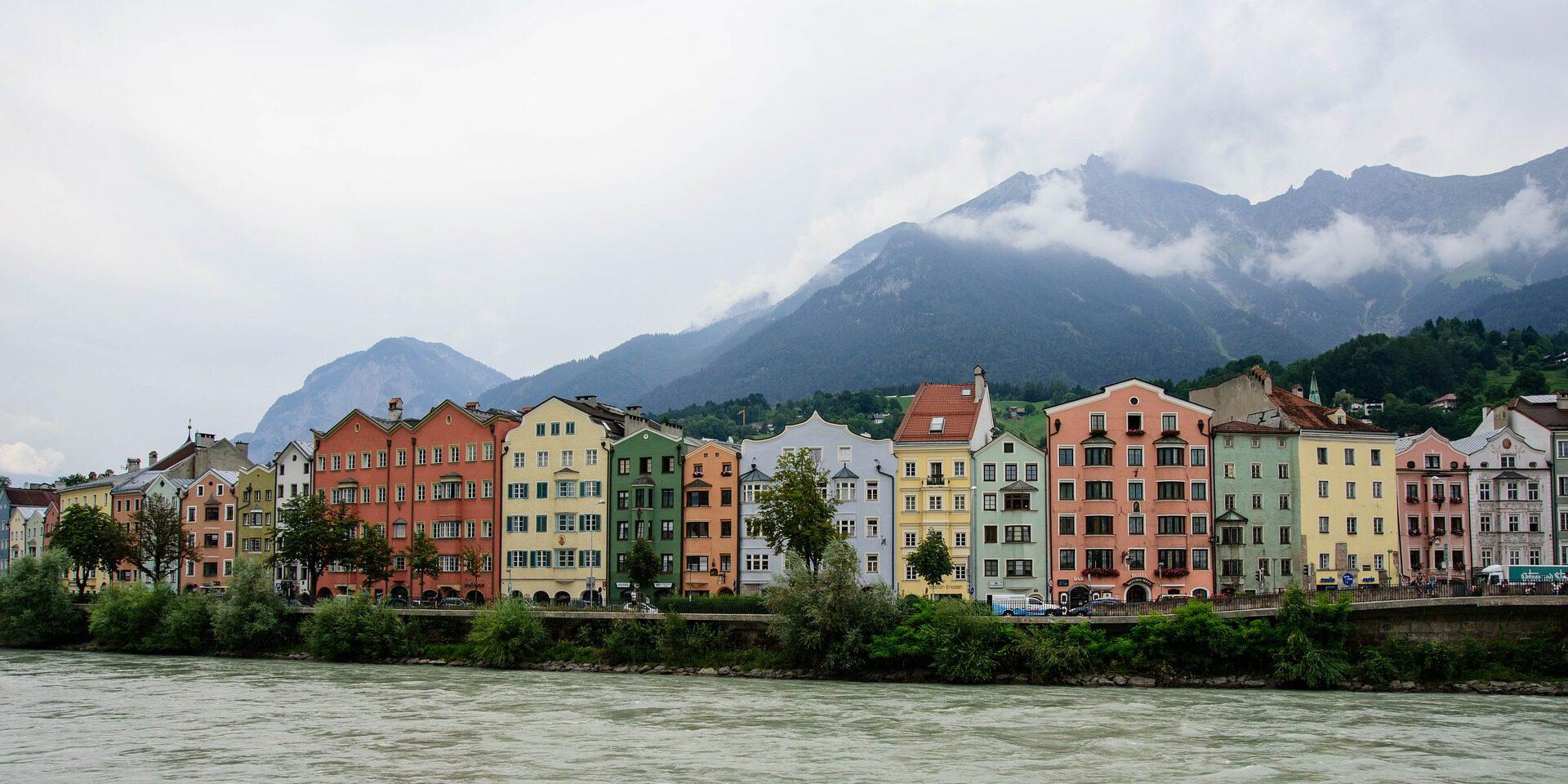 Gekleurde huizen aan rivier met bergen op achtergrond
