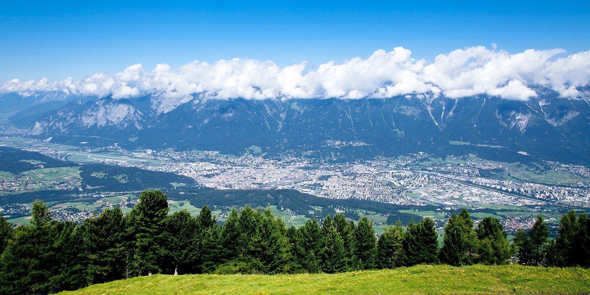 Stad in dal gezien vanaf berg met wolken er boven
