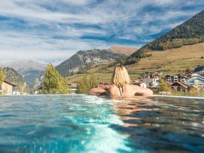 Vrouw in zwembad met uitzicht op bergen