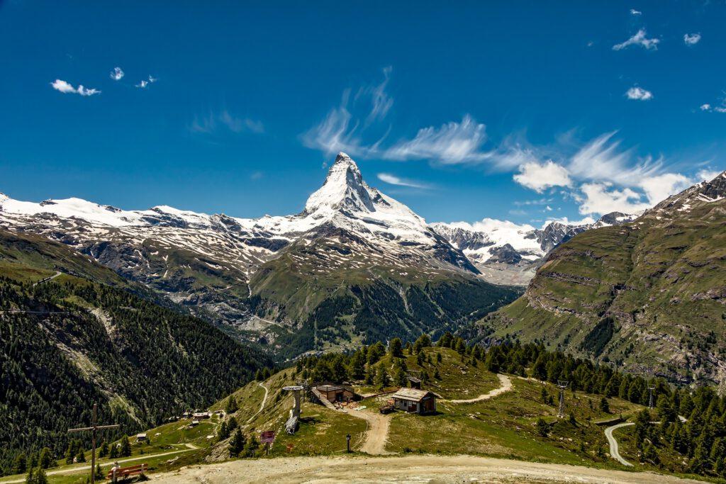 Berg met blauwe lucht en hutje op voorgrond