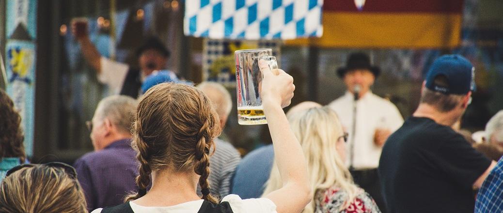 Vrouw in publiek houdt bierpul omhoog