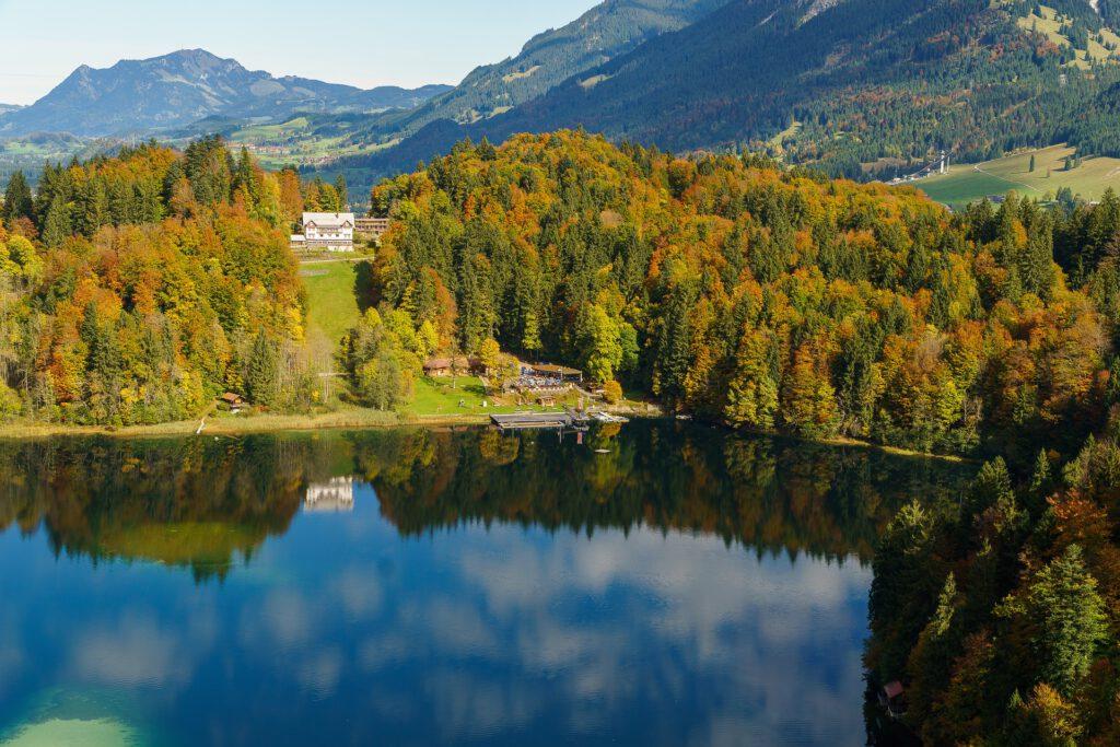 Meer met weerspiegeling van verkleurde bomen en bergen